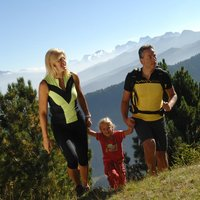 Family trekking in Val di Fiemme  - Mother, father and daughter walk happily in Val di Fiemme