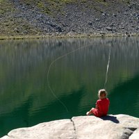 Fishing in Val di Fiemme  - Girl fishing in a mountain lake in Val di Fiemme