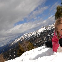 Girl posing on Cermis snow  - Joyful girl has fun posing as a model on the groomed slopes of Cermis
