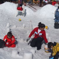 Entertainer and children on the snow of Cermis  - Entertainer keeps children busy building snow castles on Cermis